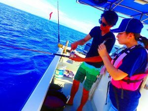 魚の釣り方を船長から教わっている