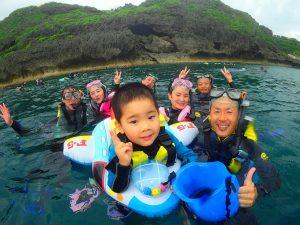子供が浮き輪に乗って上手に泳いでいる