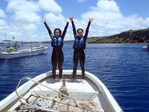 青い海を背に女性がボートで記念撮影