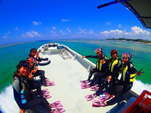 女性が6人でボートに乗って青の洞窟の前にいる
