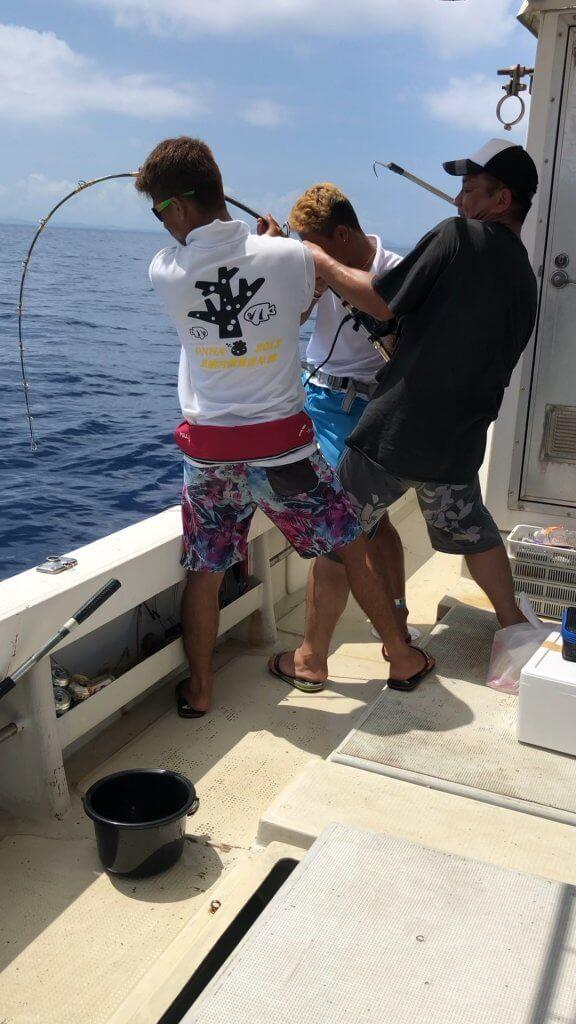 沖縄で大物が釣れて船長がサポートしている